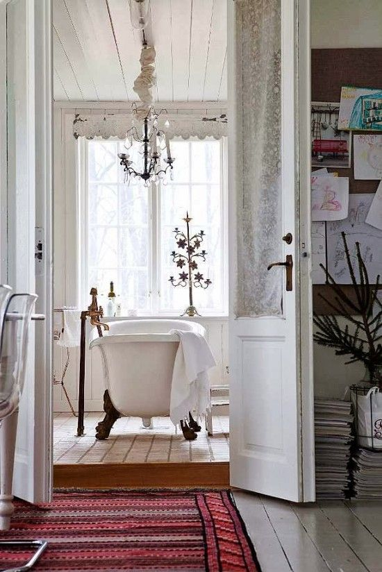 a shabby chic Scandinavian bathroom with a chandelier over the tub and vintage accessories