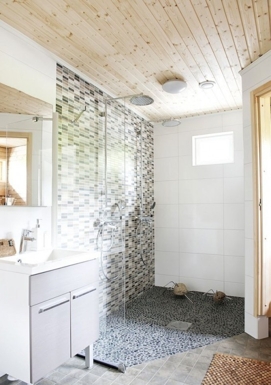 a neutral Nordic bathroom with a wooden ceiling, a mosaic tile wall and a pebble floor and an off-white vanity