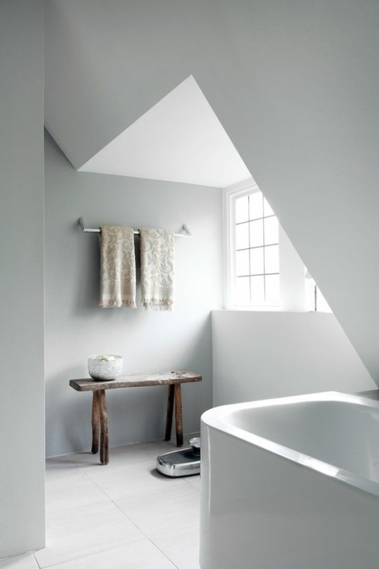 a small attic Nordic bathroom with a small tub, a bench, printed towels and much natural light