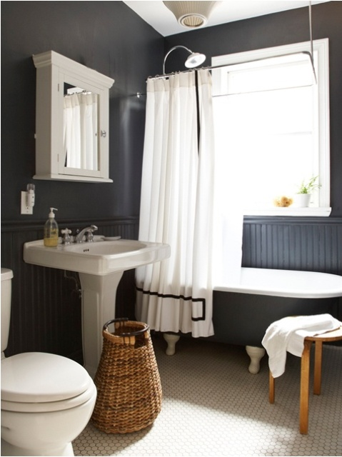a black and white Scandinavian bathroom with a vintage tub, a stool, a basket and a vintage mirror