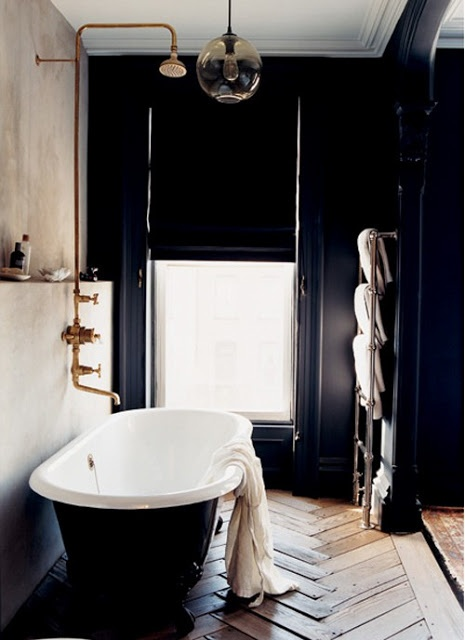 an navy art deco bathroom with a vintage tub, brass faucets and Roman shades