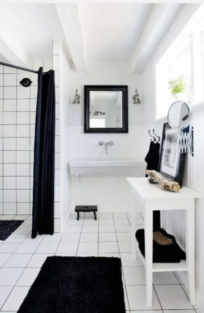 a simple Nordic black and white bathroom with black textiles, white tiles with black grout and white furniture