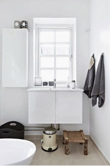 a small white Nordic bathroom with a wicker stool, a tub, a vanity and a closed storage unit