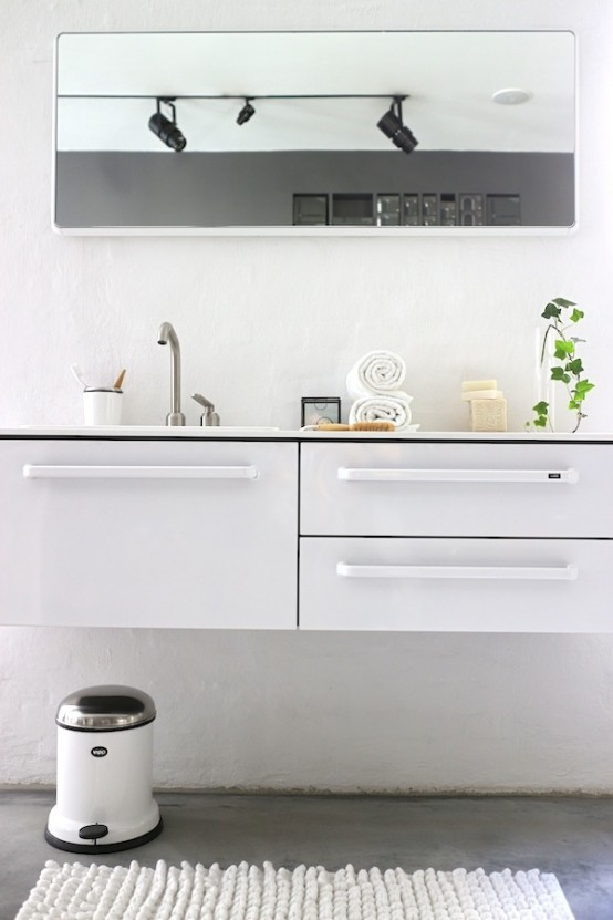 a casual Nordic bathroom with a white vanity, a large mirror, a white rug and a trash can