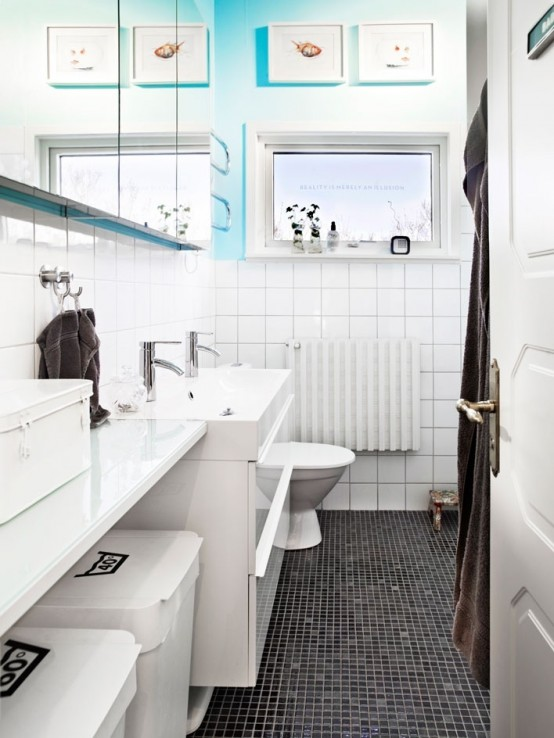 a black and white Scandi bathroom with a touch of blue and sea-inspired artworks