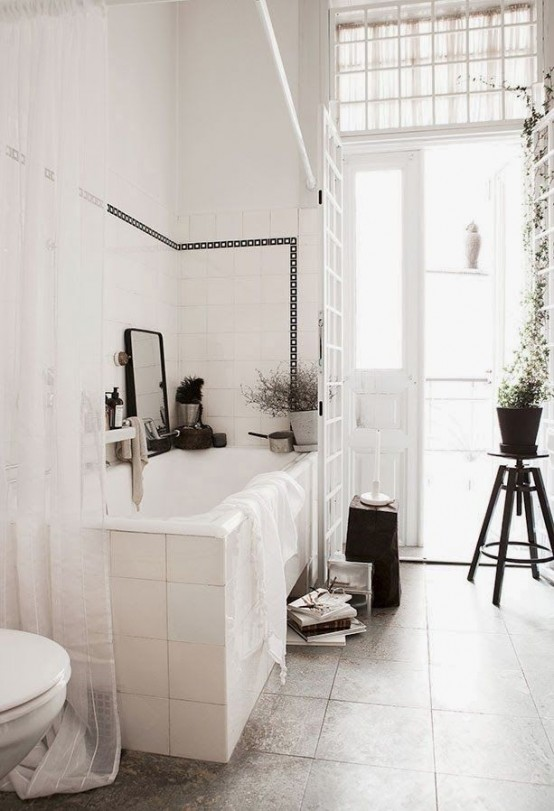 a vintage serene Scandinavian bathroom in white and grey, with vintage stools and potted greenery