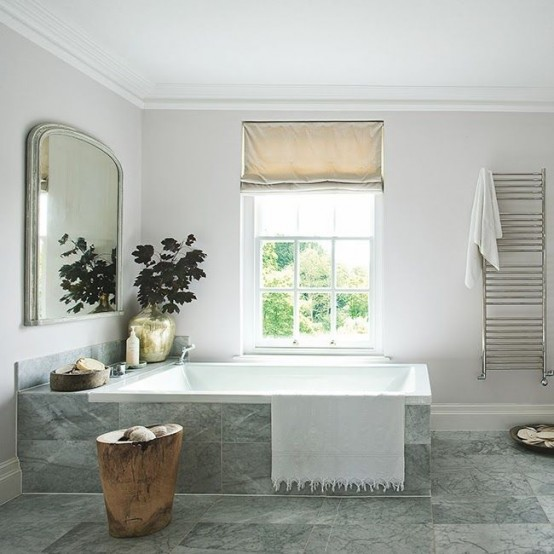 a grey and off-white Scandinaviann bathroom with Roman shades, a large mirror and a tree stump table