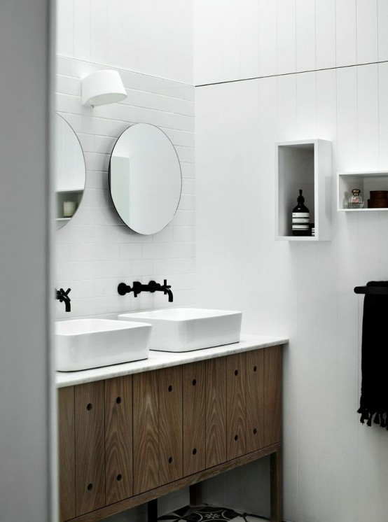 a simple Nordic bathroom done with white tiles, a wooden vanity and box shelves on the wall