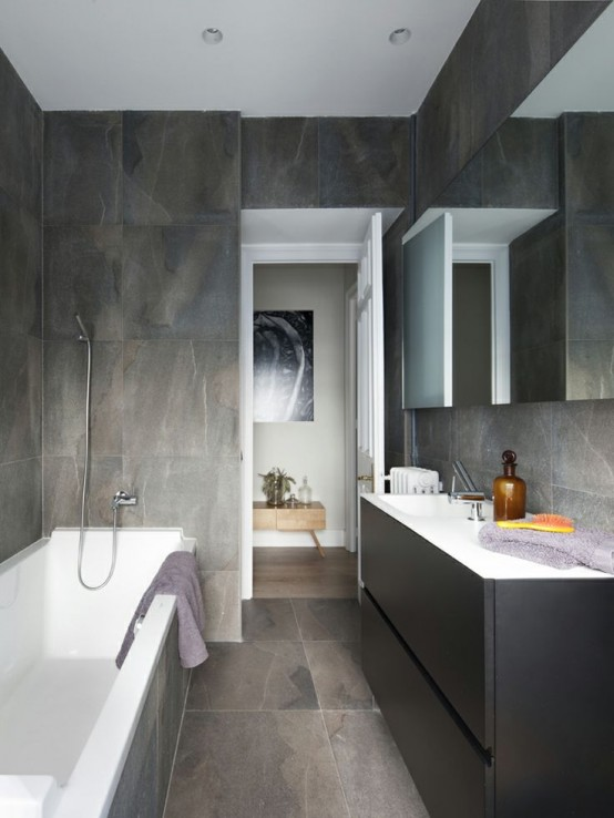 a minimalist bathroom with grey marble tiles all over, a graphite grey vanity and a large mirror