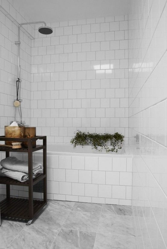 a small bathroom with white and grey marble tiles, adark stained storage unit and some potted plants