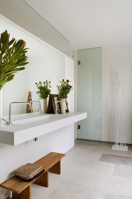 a contemporary Scandinavian bathroom done in neutrals, with potted greenery and a wooden bench