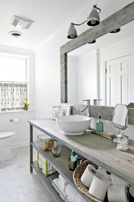 a vintage Nordic bathroom with a wooden vanity, a large framed mirror and a printed curtain on the window