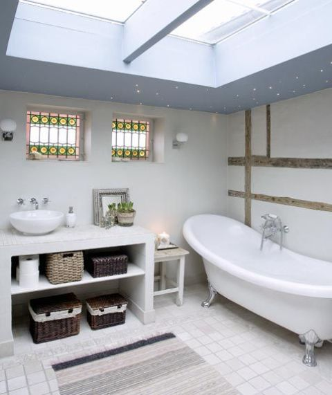 a neutral Nordic bathroom with skylights, a vanity with storage boxes and a vintage tub