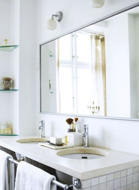 a simple Scandinavian bathroom with glass shelves, a stone countertop and white tiles