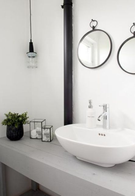 a fresh Nordic bathroom with a whitewashed wooden vanity, round mirrors and a bulb lamp