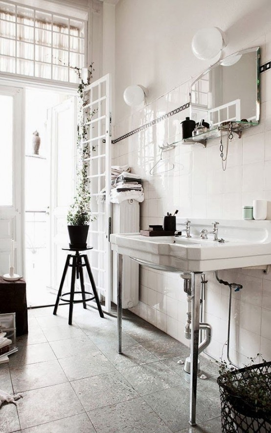a vintage Nordic bathroom with a large sink, potted greenery, much natural light and a mirror with a shelf