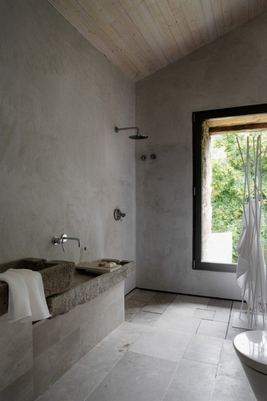a minimalist Nordic bathroom done with concrete and stone tiles, stone sinks and a large window