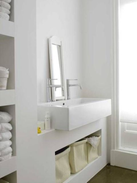 a minimalist white bathroom done with white concrete all over, a large sink and much storage space feels truly Nordic
