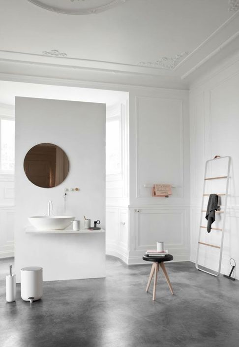 a Scandinavian bathroom with a floating vanity, a copper mirror and some modern furniture