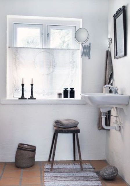 a white Nordic bathroom with a vintage feel, cadnles, mirrors and lamps plus and a basket for storage