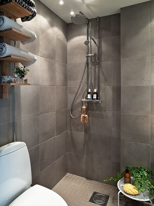 a grey Scandinavian bathroom with an open shelving unit, potted greenery and a small shower space