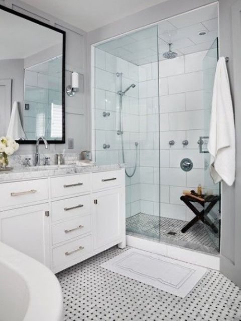 a serene white bathroom with a mosaic tile floor, a vanity with a neutral countertop and a glazed shower space
