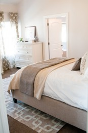 a neutral bedroom with an upholstered bed, printed textiles, simple and chic furniture is very welcoming