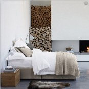 a neutral minimalist bedroom with a bed, nightstands, a fireplace and some firewood stored by it is a stylish space