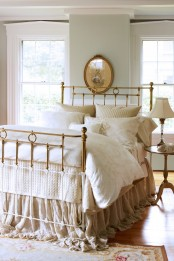a neutral vintage bedroom with grey walls, a vintage metal bed, elegant nightstand and lamps
