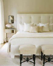 a creamy modern bedroom with a large and comfy bed, upholstered stools and mirror nightstands and mirrors over them