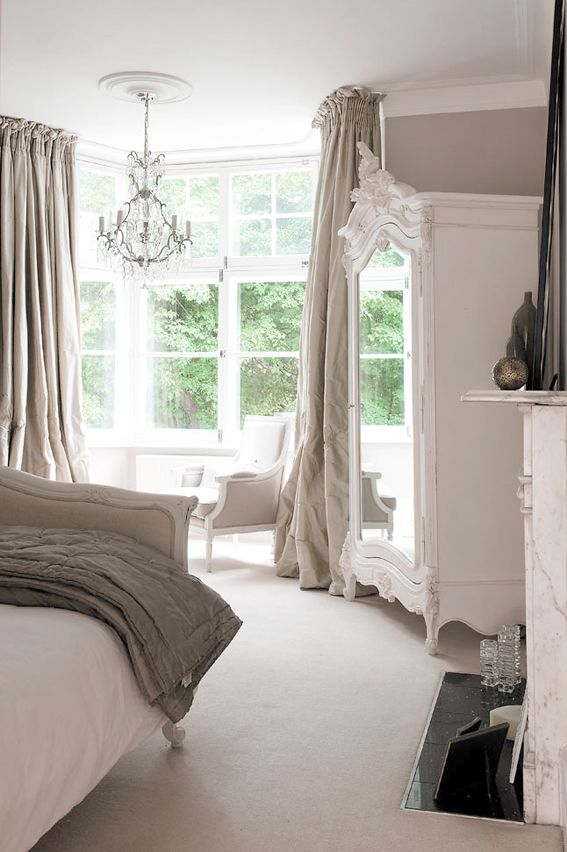 a neutral vintage bedroom done in white and greys, refined furniture, a crystal chandelier, grey linens