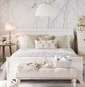 a neutral bedroom with a wallpaper wall, elegant white furniture, printed bedding, nightstands and lamps that ligth up the space