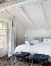 a white attic bedroom with a bed, black leather stools and a brown rug for a drama and a contrast
