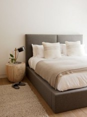 a contemporary neutral bedroom with a grey upholstered bed, neutral bedding and rugs, a wooden nightstand for a chic look