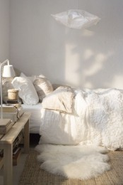 a neutral bedroom with white walls and layered bedding, faux fur, a wooden table with books and lamps instead of a nightstand