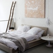 a neutral bedroom with a grey upholstered bed, mismatching nightstands, a ladder, an artwork