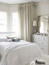 a neutral bedroom with soft-colored textiles, a mirror on a sideboard, neutral layered bedding is cool and chic