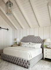 a neutral attic bedroom with a grey upholstered bed, white nightstands, pendant lamps and table ones