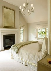 a warm-colored neutral bedroom with a fireplace, an oversized fireplace, a bed and a vintage bedroom