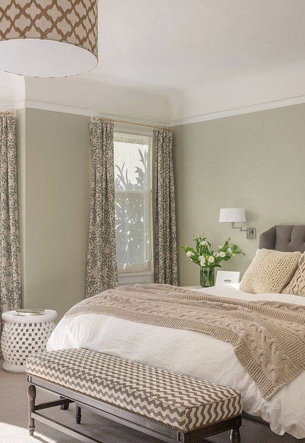 a neutral and muted color bedroom with green walls, a bed with various neutral bedding, a pendant lamp and printed bench