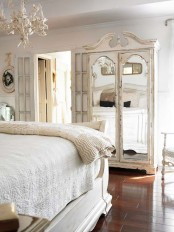 a neutral vintage bedroom with refined furniture, a mirror wardrobe, a white chandelier, layered bedding and pretty artworks