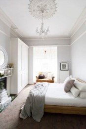 a neutral bedroom with white walls, molding on the ceiling, a wooden bed and a mustard chair, a fireplace and some books