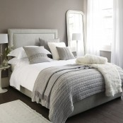 a simple neutral bedroom with taupe walls, neutral furniture, layered bedding, a mirror and lamps plus a neutral rug