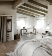 a neutral vintage bedroom with wooden beams, refined wooden furniture, a built-in wardrobe, neutral linens and table lamps