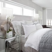 a neutral bedroom with a creamy bed, white and grey bedding, mirror nightstands and potted orchids looks glam and chic