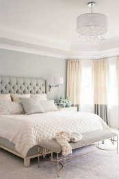a neutral bedroom with grey walls, a chic bed with a tufted headboard and color block curtains and a crystal chandelier