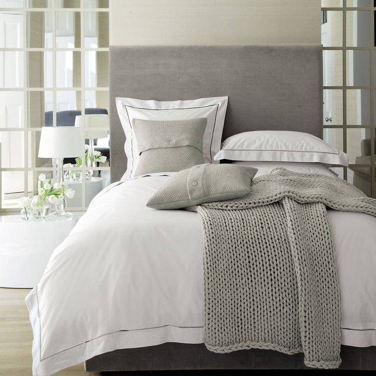 a modern bedroom with mirror panels, a grey bed, layered bedding and knit and crochet items is very light filled