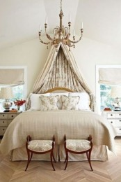 a neutral refined bedroom with a neutral bed, a floral canopy, a refined chandelier, exquisite stools