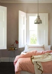 a mid-century modern neutral bedroom with a cool nightstand, a red lamp, a bed with pink striped bedding and cozy blankets is very chic