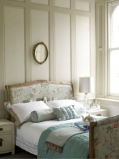 a romantic vintage bedroom done in neutrals, with paneled walls, a floral bed, neutral furniture, powder blue and neutral bedding and ruffled pillows